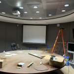 Projection screen with a projector in a round conference room while still under construction