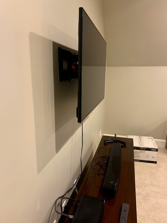 tv mounted on the wall using an articulating tv mount with one hdmi cable left outside the wall connected to the av receiver