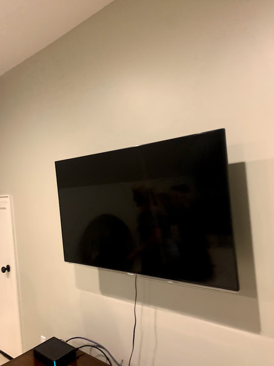 tv mounted on the wall with one hdmi cable outside the wall going to the cable box